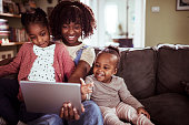 Close up of a mother using a tablet with her daughters