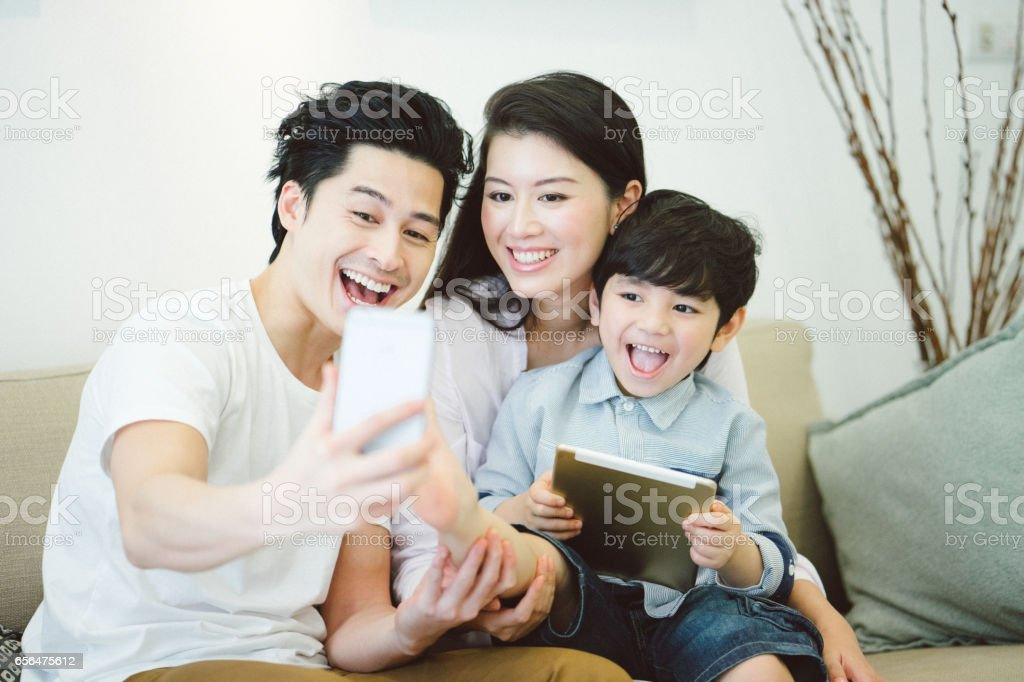 Young family using technological devices stock photo