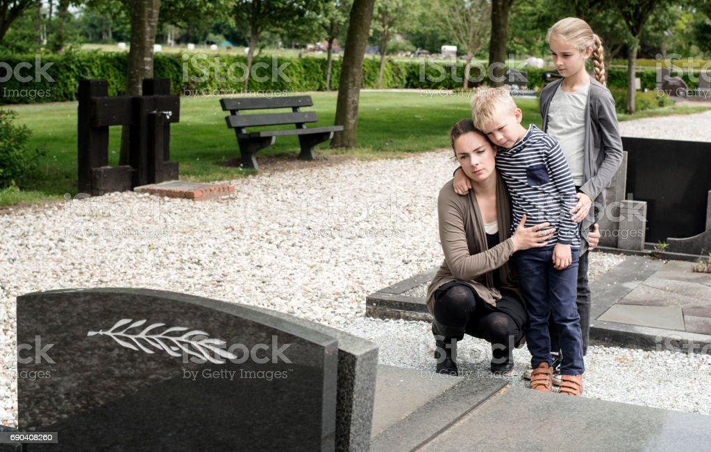 Young family visiting grave of family stock photo