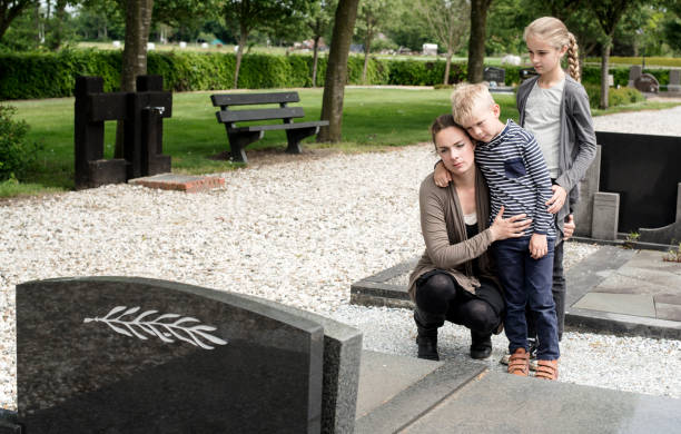 young family visiting grave of family - grief stock photos and pictures