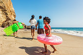 Photo of a young African American family walking on California beach, primary focus on young girl in the foreground laughing as she runs with an inner tube water toy.