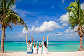 Happy beautiful family on white beach having fun raising their hands up