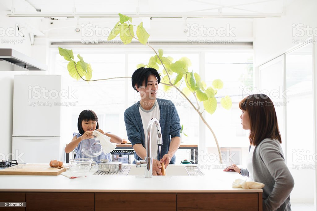 Young family washing dishes together in the kitchen stock photo