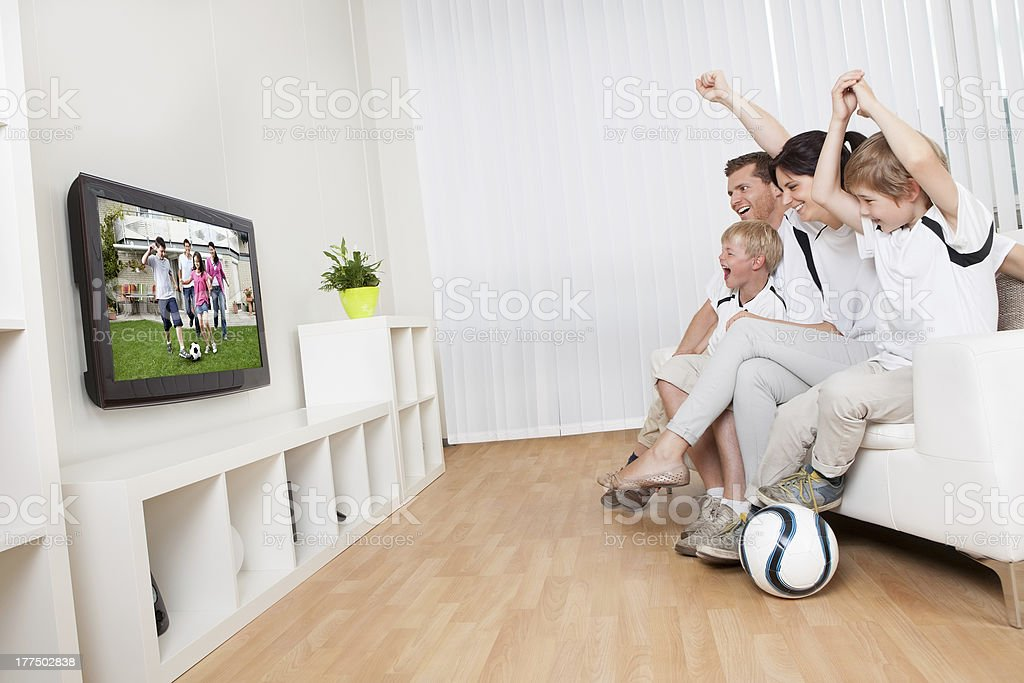 Young family watching football - Royalty-free Adult Stock Photo