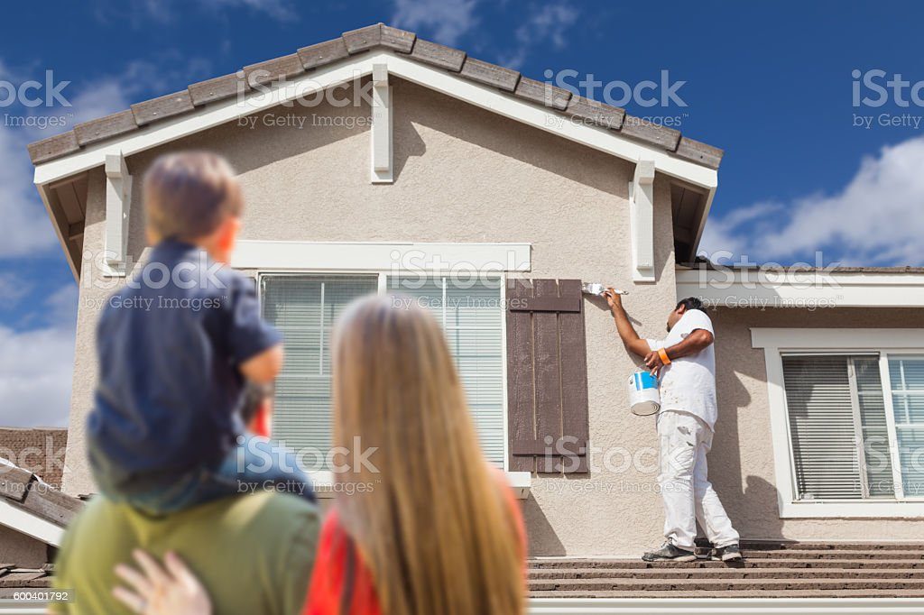 Young Family Watching House Get Painted by Painter stock photo