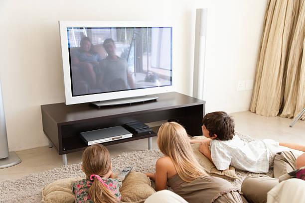 eine junge familie vor dem fernseher - kids tv zimmer stock-fotos und bilder