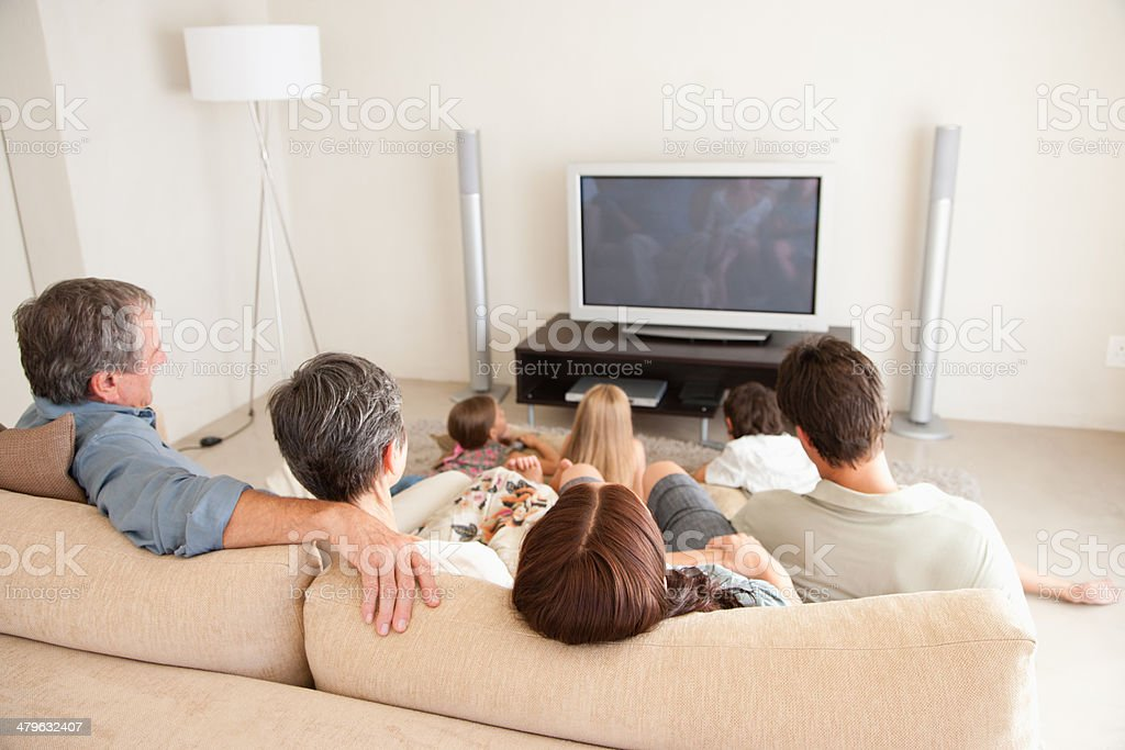 A young family watching television with grandparents stock photo
