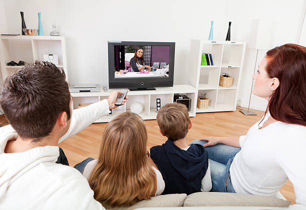 young family watching tv at home - family watching tv stock photos and pictures