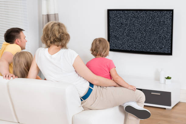 young family watching tv together - tv e familia e ecrã imagens e fotografias de stock