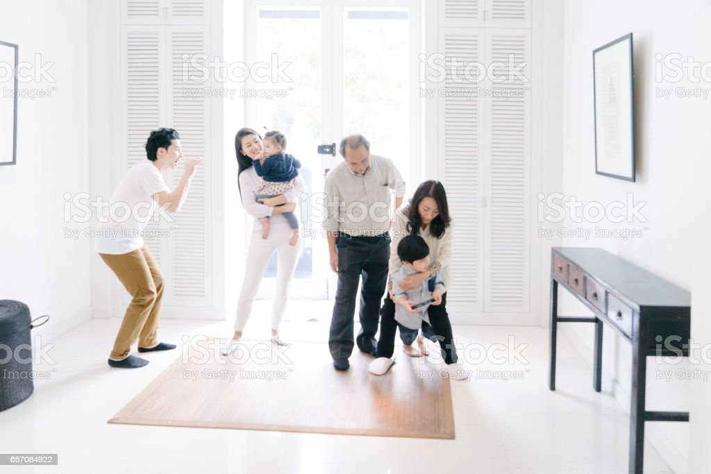 Young family welcoming grandparents at home stock photo
