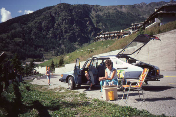 Young family with a light blue Saab 900 enjoying a picnic in the Swiss Alps. Lac Léman, Switzerland - July 1982: Vintage analog camera image of a young family driving a light blue Saab 900 during summer vacation having a picnic in the Swiss Alps. saab stock pictures, royalty-free photos & images