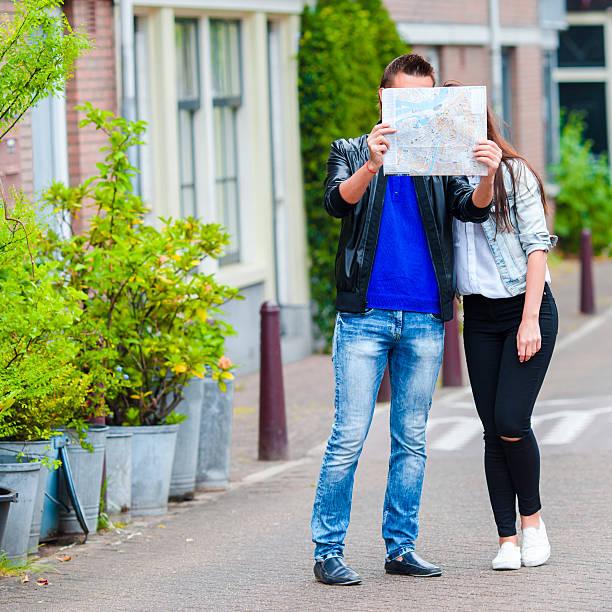 junge familie mit einer karte im freien in amsterdam - hochzeitsreise amsterdam stock-fotos und bilder
