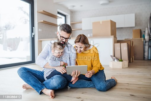 istock A young family with a toddler girl moving in new home, using tablet. 1135086412