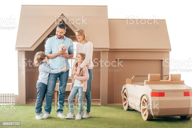 Young family with adorable puppy on yard of cardboard house isolated picture id936397202?b=1&k=6&m=936397202&s=612x612&h=vaakx24kimuulnww a2q8kvxxesbbpqxxki2rdwakb4=