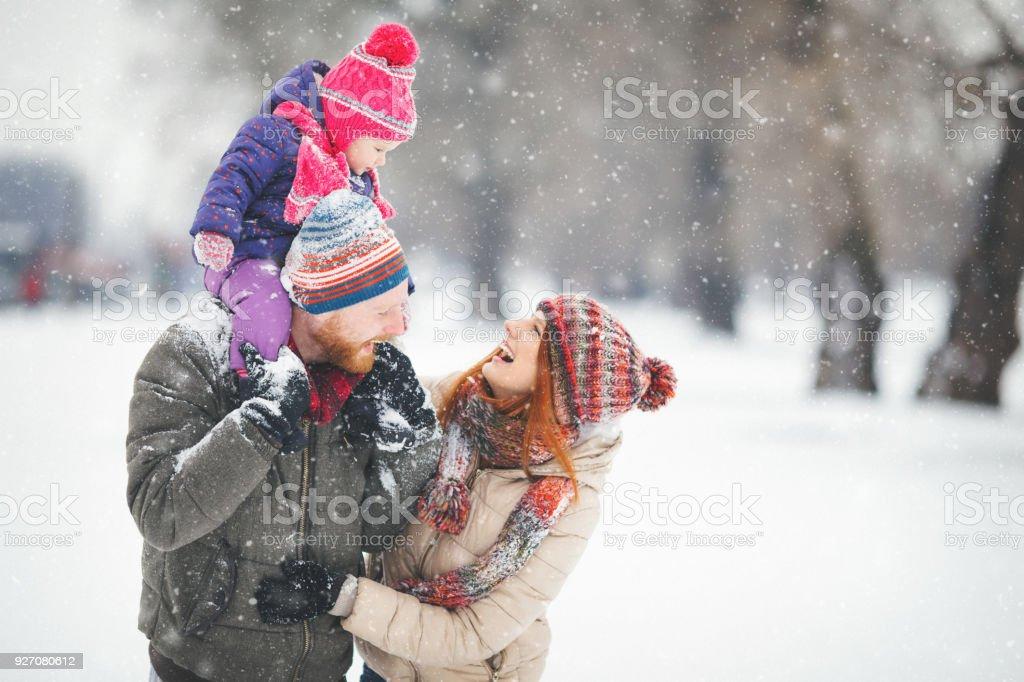 Junge Familie mit Babymädchen, die Spaß im Schnee – Foto