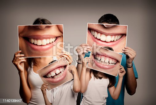 young family with children holding a picture of a mouth smiling on a gray background