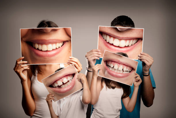young family with children young family with children holding a picture of a mouth smiling on a gray background teeth stock pictures, royalty-free photos & images