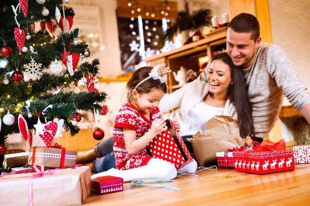 young family with daughter at christmas tree at home. - christmas families stock photos and pictures