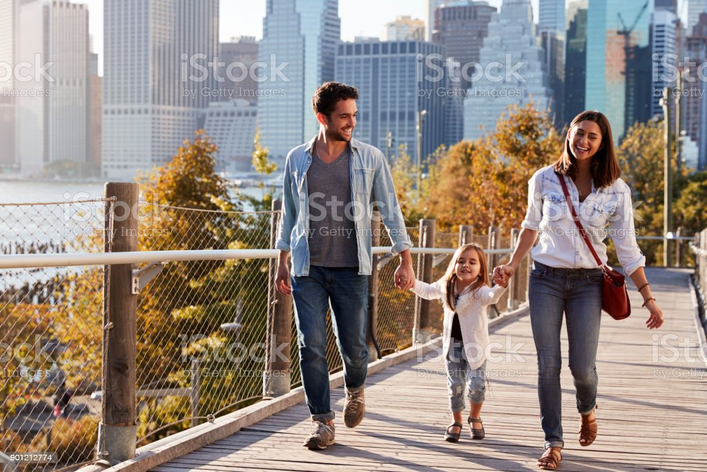 Young family with daughter taking a walk on footbridge royalty-free stock photo