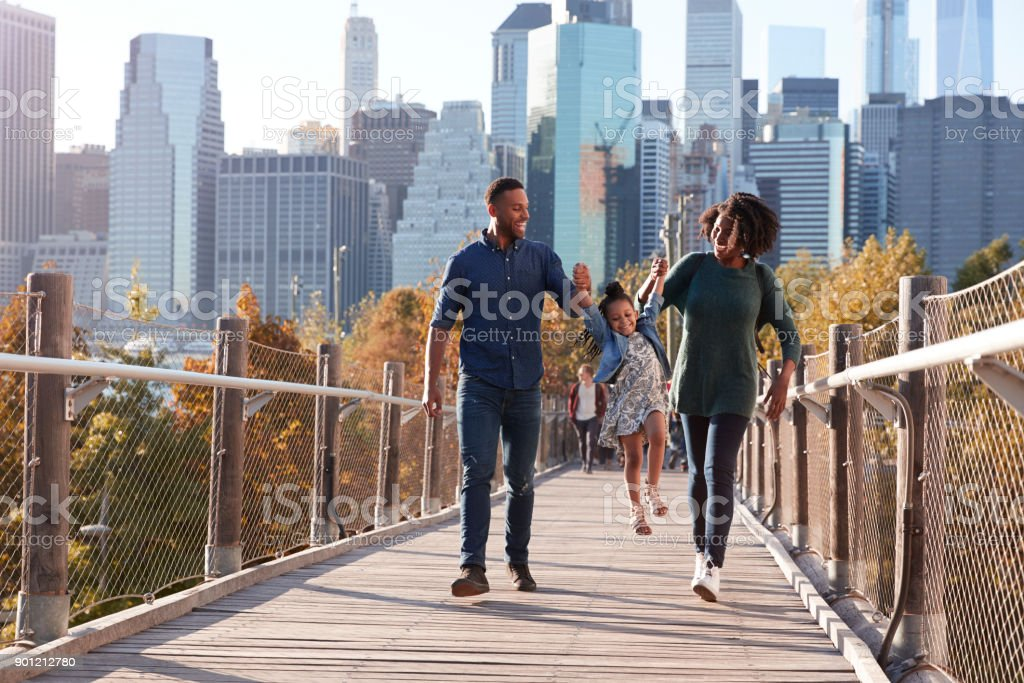 Young family with daughter taking a walk on footbridge stock photo