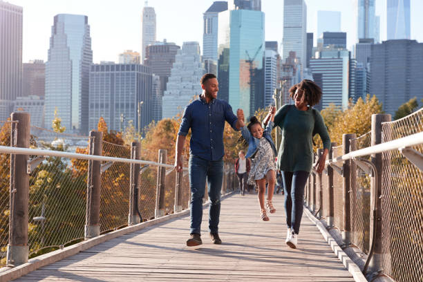 young family with daughter taking a walk on footbridge - family vacation stock photos and pictures