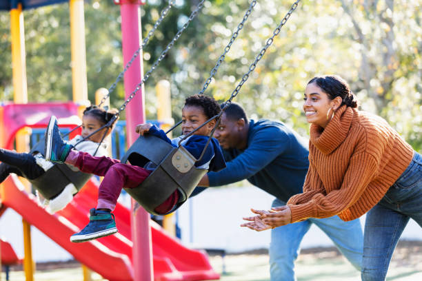 Young family with twins on playground swings stock photo