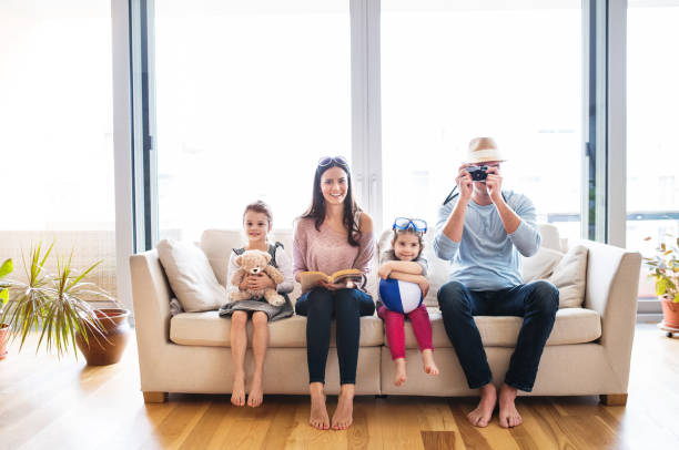 young family with two children getting ready for holiday. - happy mom packing some toys stock photos and pictures