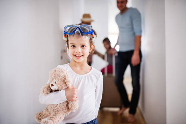 young family with two children going on a holiday. - happy mom packing some toys stock photos and pictures