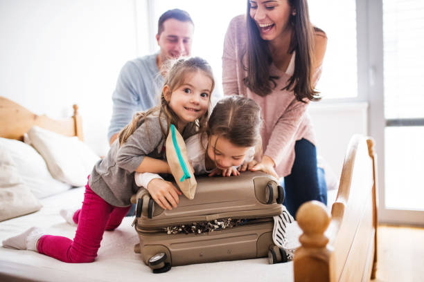 młoda rodzina z dwójką dzieci pakuje się na wakacje. - hotel zdjęcia i obrazy z banku zdjęć