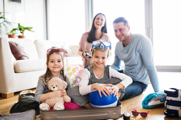 young family with two children packing for holiday. - happy mom packing some toys stock photos and pictures