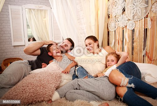 479612990istockphoto Young family with two children relaxing together at home on bed 868555666