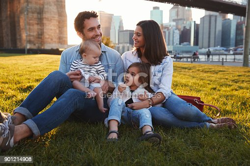 istock Young family with two daughters sitting on lawn, close up 901214908