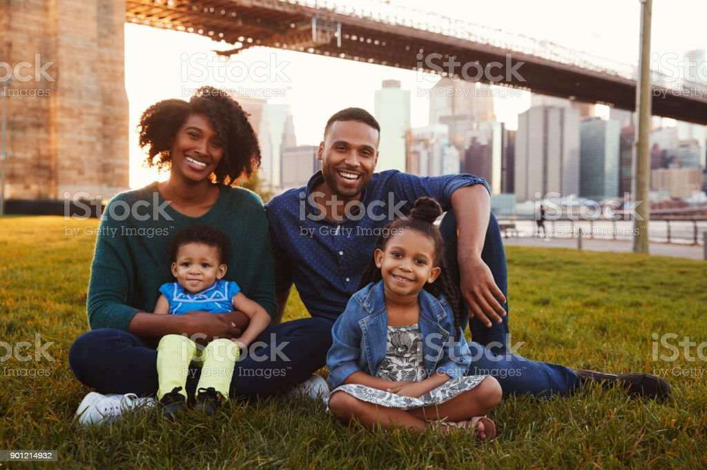 Young family with two daughters sitting on lawn, close up stock photo