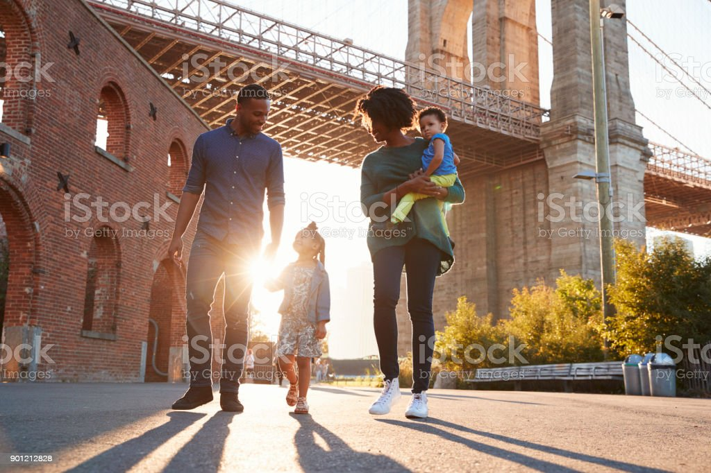 Young family with two daughters walk on a street stock photo