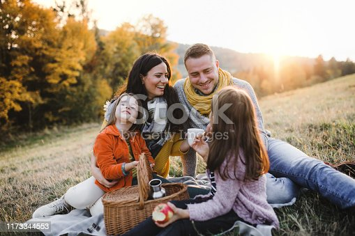 A portrait of happy young family with two small children sitting on a ground in autumn nature at sunset, having picnic.