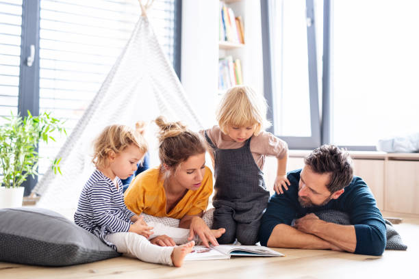 Young family with two small children indoors in bedroom reading a book. stock photo