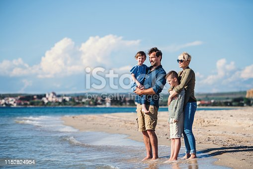 Young family with two small children standing barefoot outdoors on beach.