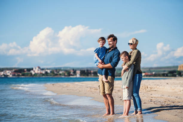 Young family with two small children standing outdoors on beach. stock photo