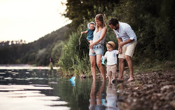 A young family with two toddler children outdoors by the river in summer. A young family with two toddler children spending time outdoors by the river in summer. lake stock pictures, royalty-free photos & images