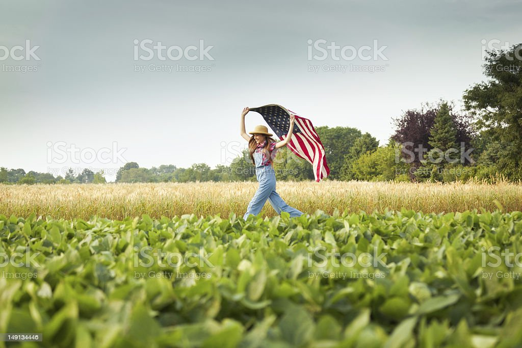 Young Farm Girl Running Across Field with USA Flag stock photo