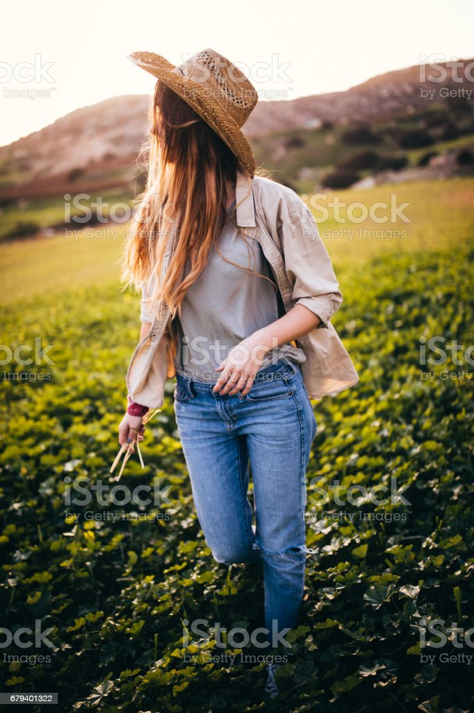 Young farm girl walking amongst green crops royalty-free stock photo