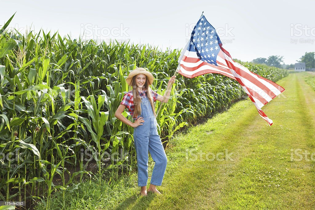 Young Farm Girl Waving U.S. Flag Along the Field stock photo