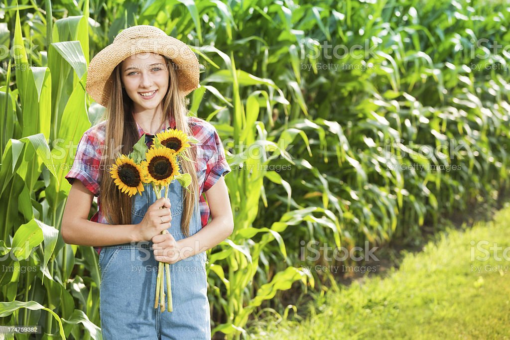 Young Farmer Girl with Sunflowers by the Farm Field royalty-free stock photo
