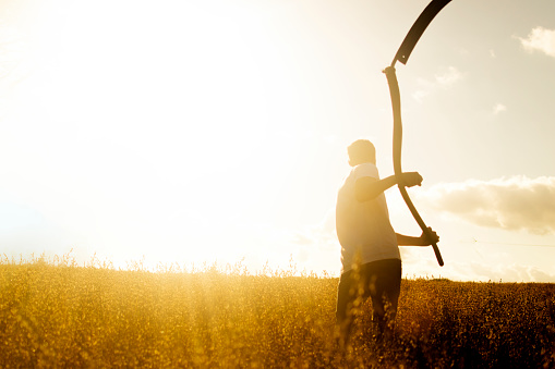Young farmer in a sunny field with scythe