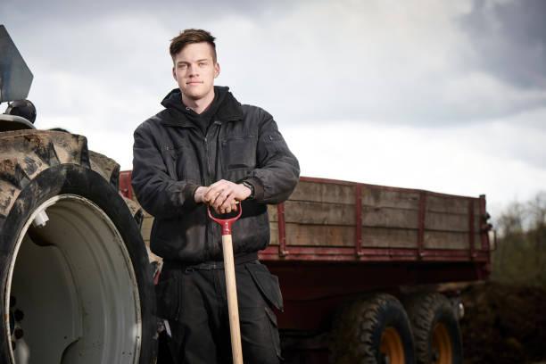 junger landwirt vor seinem blauen traktor - bauernberuf stock-fotos und bilder