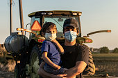 istock Young farmer posing with his son, both wearing protective face masks 1227224850