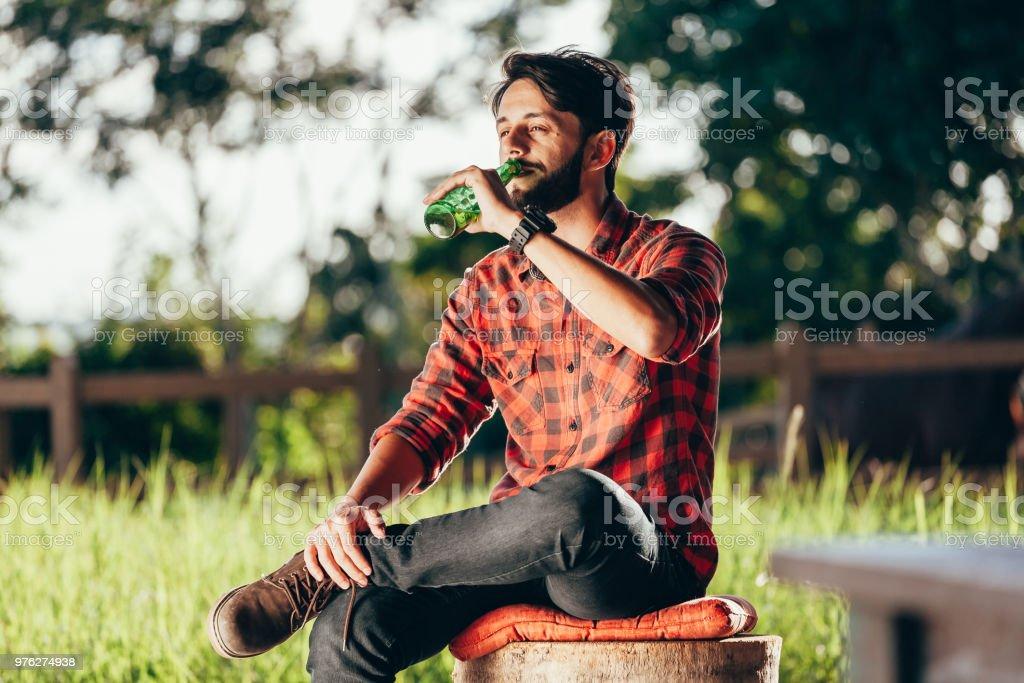 Jungbauer auf Bank sitzen und trinken Bier mit Weide und Koppel im Hintergrund – Foto