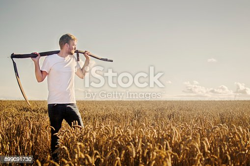 A young farmer rests with a scythe over his shoulders in his fields which are ripe with crops, on a sunny evening.