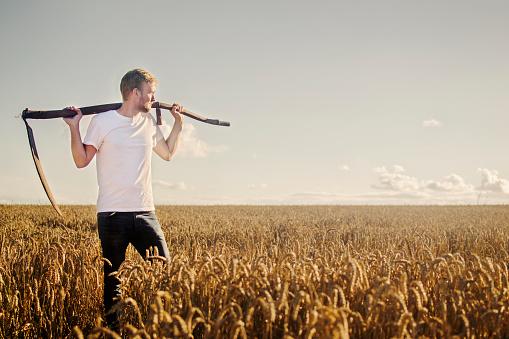 Young farmer with scythe
