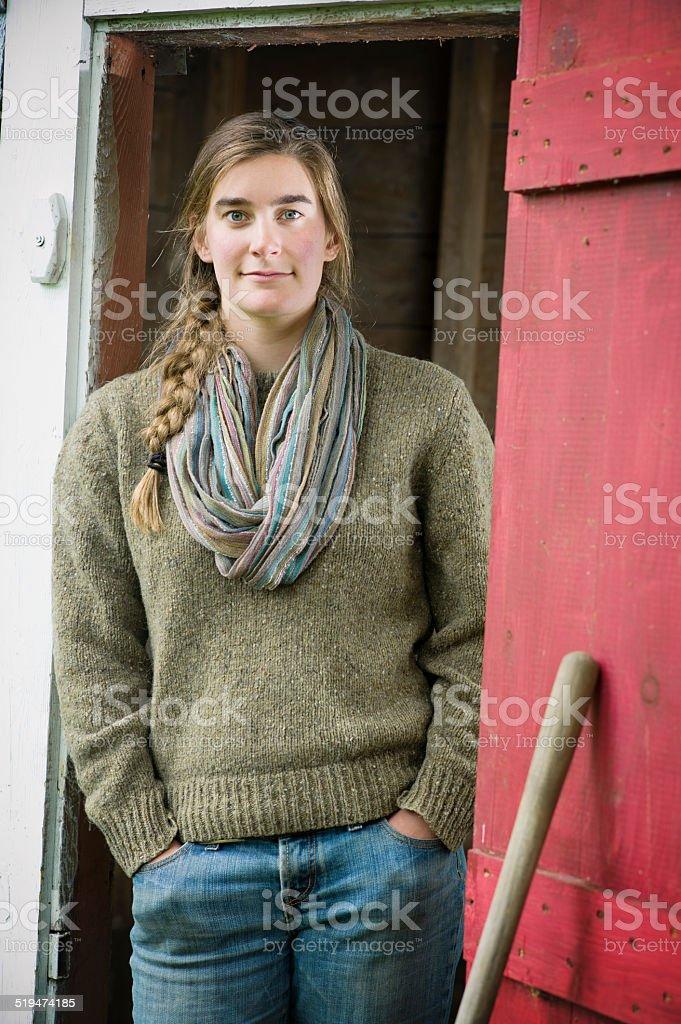Jeune agriculteur femme dans une grange. - Photo